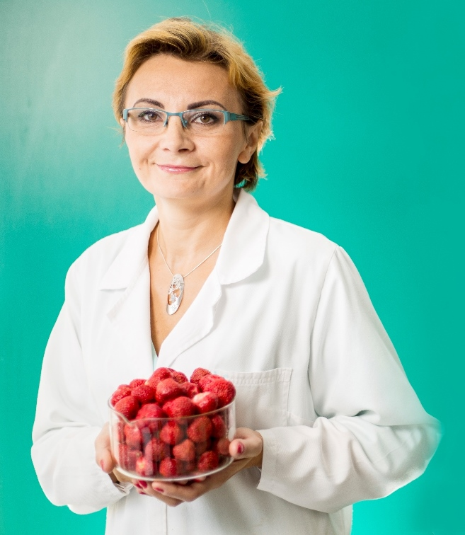 Dr Eng. Agnieszka Ciurzyńska portrait photo on a green background. In her hands she holds a glass dish filled with strawberries.