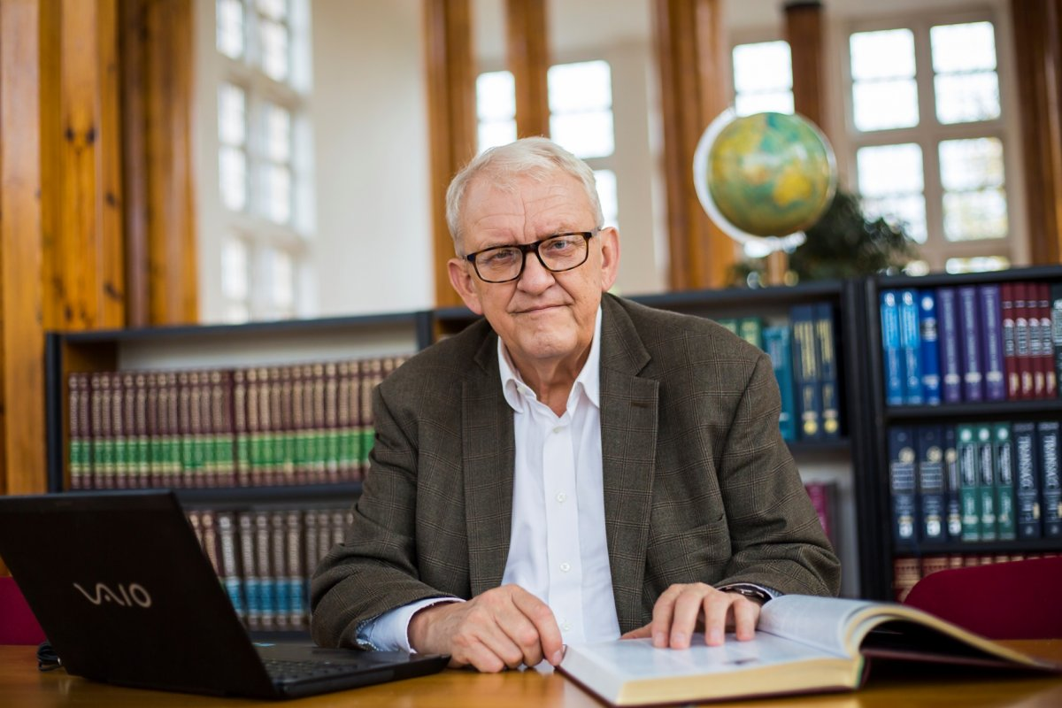 Prof. Juliusz Gardawski - portrait photo on the background of bookshelves. In front of the Professor there is a laptop and an open book on the table